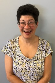 Head shot of Liz Weintraub smiling wearing glasses in front of a grey wall