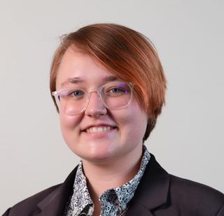 Nina Erbes, a white person with glasses and short reddish-brown hair, smiles at the camera. She wears a black blazer and a black and white button-up shirt.