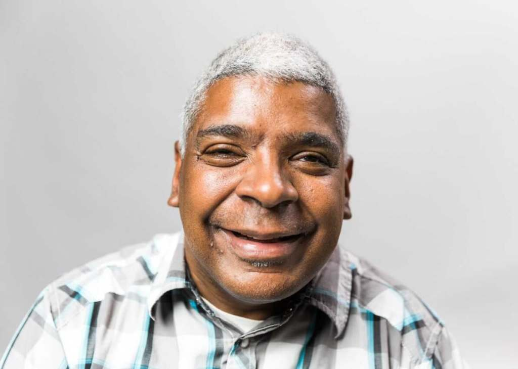 Headshot of Joe Basey, male of color with white hair and a plaid shirt