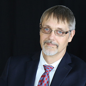 Image of John Tschida a while man with glasses greying hair and mustache wearing a black suit and red tie with white shirt smiling in front of black background.