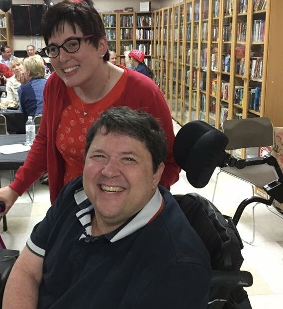 A picture of Jamie and Frank. Jamie standing behind Frank - white woman smiling wearing glasses, short brown hair and red shirt and sweater. Frank - white man smiling with short brown hair and blue polo shirt with part of his wheelchair head rest and back showing. They are standing in front of bookcase.