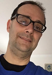 Image of Phil Weintraub. White man with glasses brown hair wearing a black and blue shirts