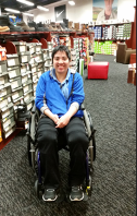 Image of Agatha Gietzen. White woman in wheel chair blue shit and black pants smiling in front of shoe aisle.