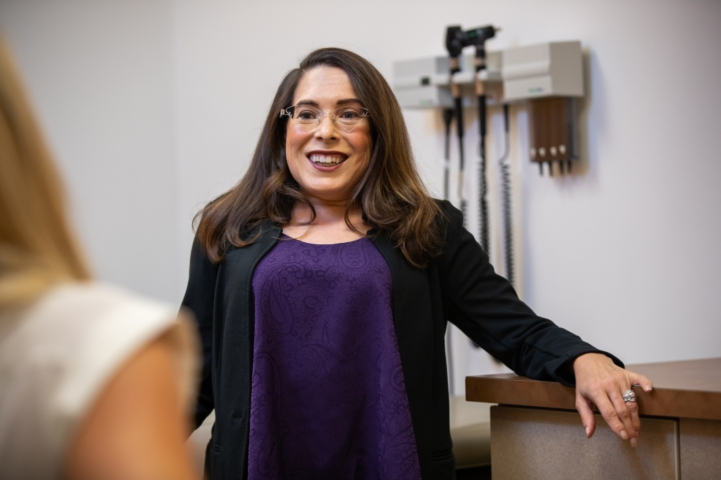 picture of the author, Amy Houtrow, in a purple shirt and black sweater in a doctor's office