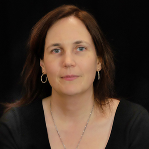 image description: picture of Rylin Rodgers, a white woman with dark brown hair wearing a black shirt in front of a black background