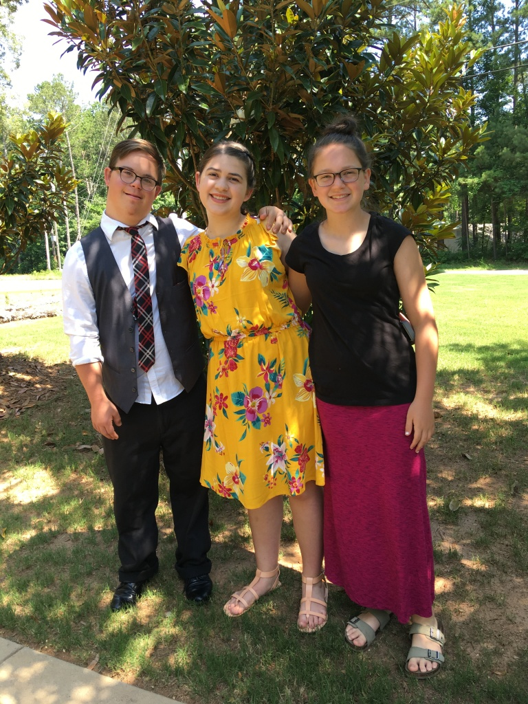 Andy, Kate, and Lily Meredith stand together outside with trees and grass in the background.