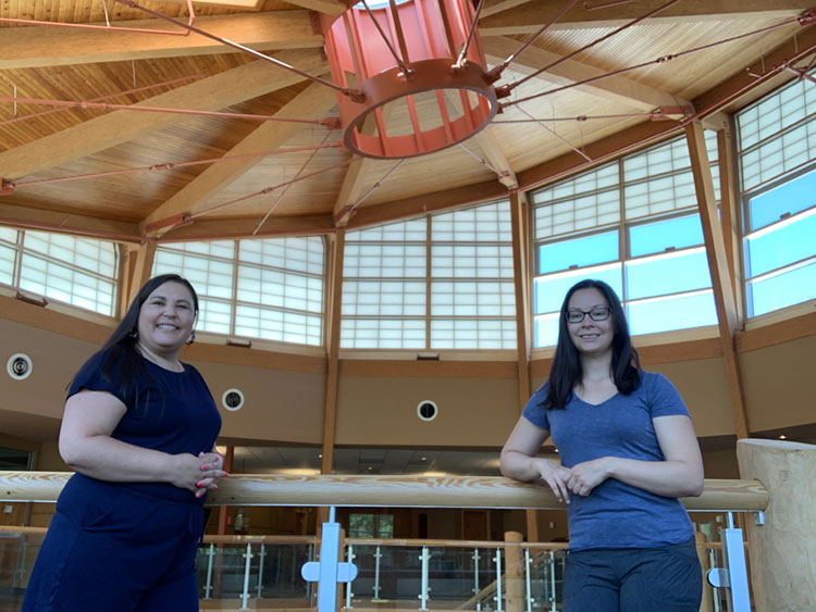 Salena standing in a blue dress and Helen standing in a blue t-shirt and jeans. The background is a large room with a wooden ceiling.
