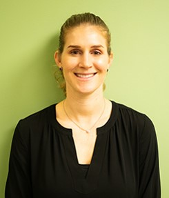 the author: a white woman with brown hair in a ponytail and brown eyes, wearing black shirt in front of green wall