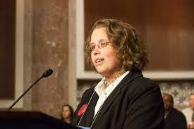 White woman with light curly hair and glasses, speaking at podium